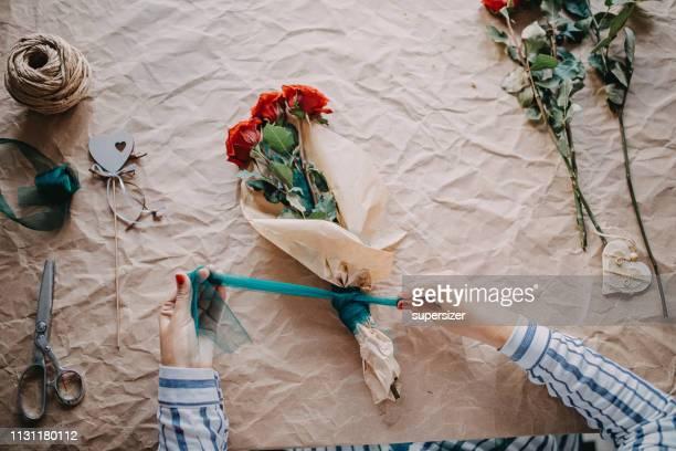 le mani delle donne avvolgono un mazzo di rose in carta - composizione di fiori foto e immagini stock