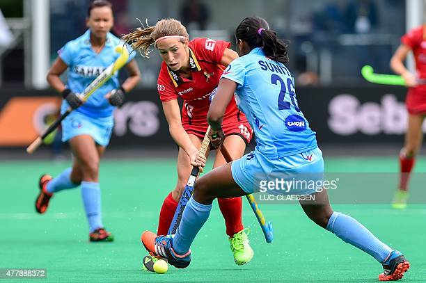 Women's hockey players India's Sunita Lakra and Belgium's Barbara Nelen are pictured in action during the Group B match between Belgium and India at...