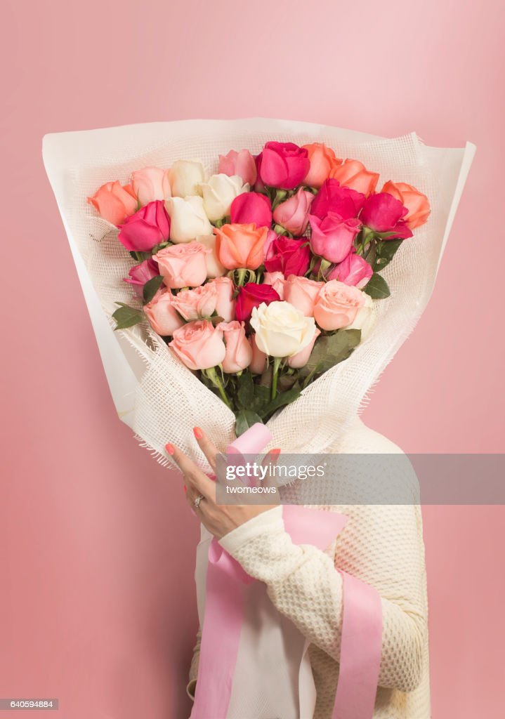 Women's in casual wear holding a big bouquet of roses covering face on pink background. Studio shot.