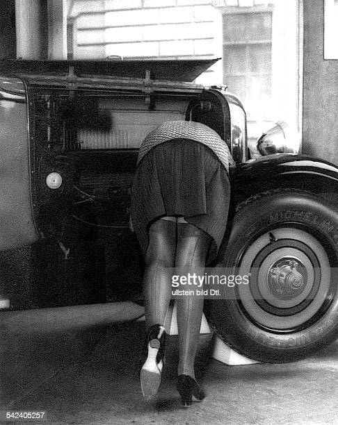 Women's legs 'The car breakdown' woman bending over the engine bonnet and showing her legs with seamed stockings 1929 Published by 'Uhu' 6/1929...