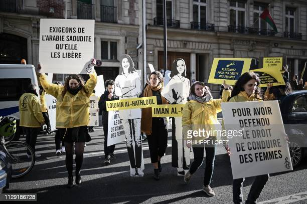 Women's rights activists hold signs as they take part in a demonstration organized by Amnesty International outside the Saudi Arabia embassy in Paris...