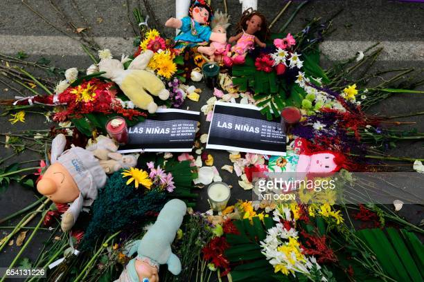 Women's rights activists place flowers and dolls in homage to the victims in a protest outside the Guatemalan Embassy in Managua on March 16 2017 to...