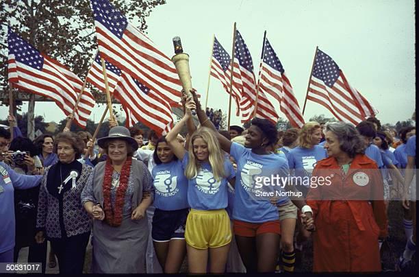 Women's rights advocates Susan B Anthony II Bella Abzug Peggy Kokernot wearing yellow shorts Betty Friedan wearing red coat leading a flag waving...