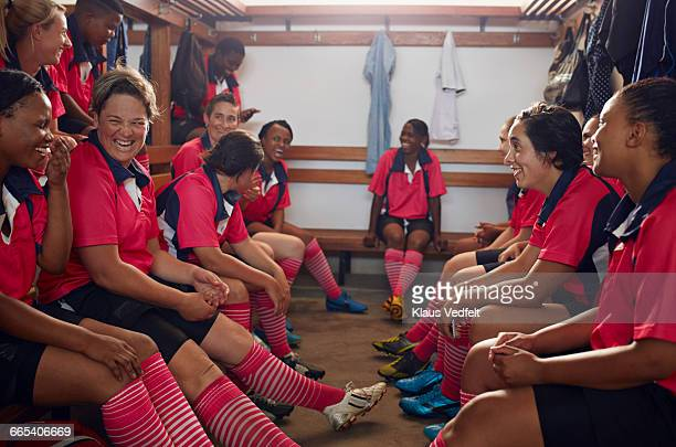 womens rugby players laughing together before game - rugby players in changing room stock photos and pictures