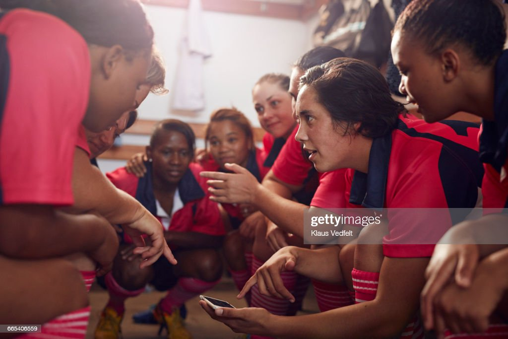 Womens rugby players looking at phone before game : Stock Photo