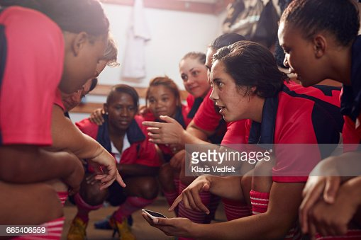 Womens rugby players looking at phone before game