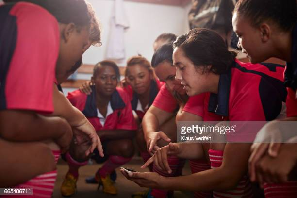 womens rugby players looking at phone before game - rugby team stock pictures, royalty-free photos & images