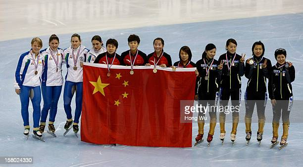 Women's shorttrack relay team members of Italy China and Japan pose at the ceremony of the Women's 3000m Final during the day two of the ISU World...