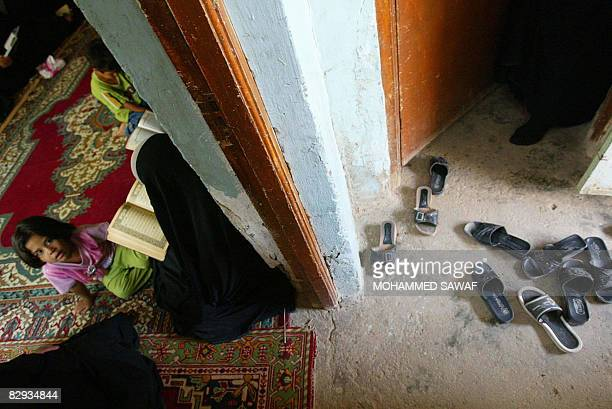 Women's slippers are left at the door as Shiite Mulsim women read the holy Muslim Koran together in the southern holy city of Karbala some 120...