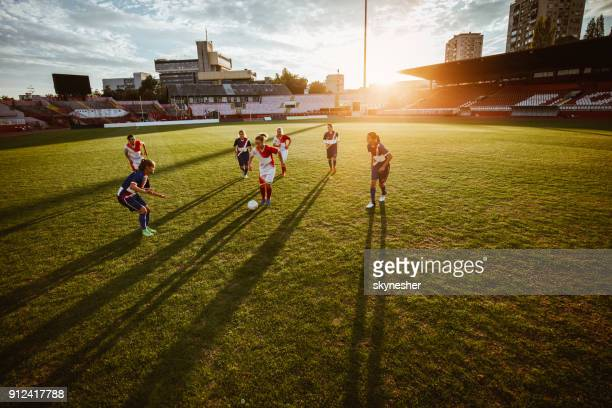 women's soccer match on a stadium at sunset! - soccer competition stock pictures, royalty-free photos & images