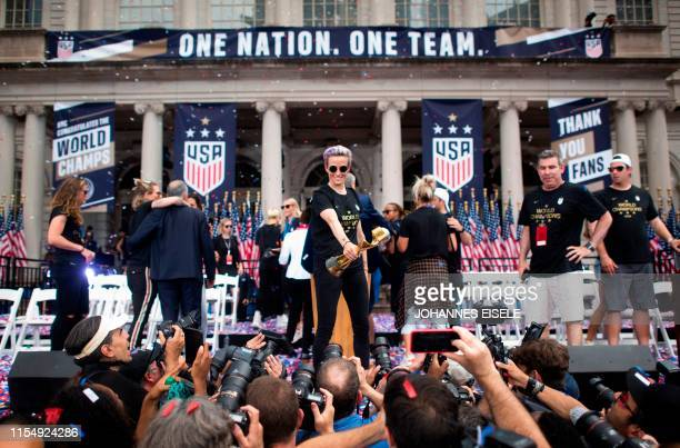 Women's soccer player Megan Rapinoe holds the trophy in front of the City Hall after a ticker tape parade for the women's World Cup champions on July...