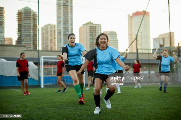 women's soccer team celebrates scoring a goal in a competition. - soccer competition stock pictures, royalty-free photos & images