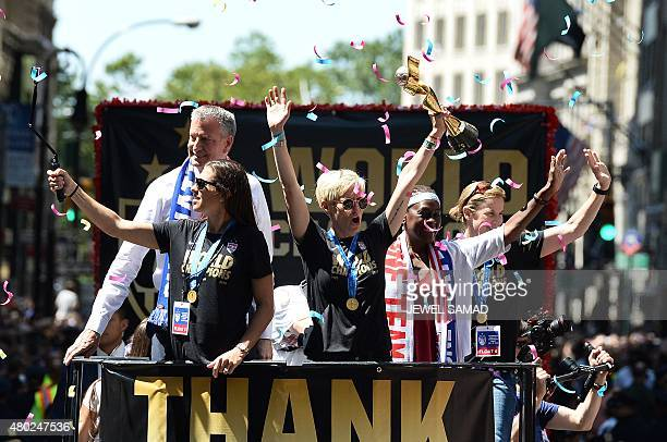 USA women's soccer team midfielder Megan Rapinoe holds up the World Cup 2015 trophy as midfielder Carli Lloyd New York City Mayor Bill de Blasio and...