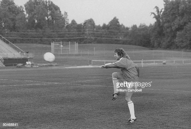 US Women's Soccer Team star Michelle AkersStahl in uniform kicking ball as she warms up on soccer field before exhibition game w the Chinese National...
