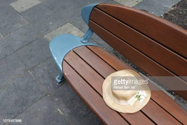womens straw hat on a wooden street bench - rafael ben ari - fotografias e filmes do acervo
