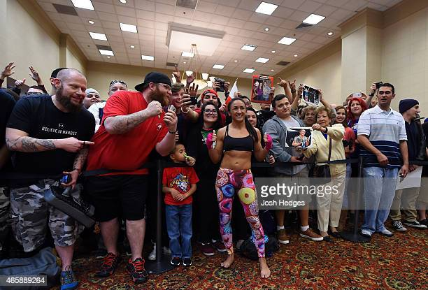 UFC women's strawweight champion Carla Esparza poses for photos with fans after an open training session for fans and media at the Hilton Anatole...