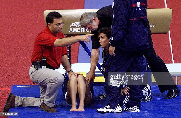 Women's Team Coordinator Bela Korolyi comforts Shannon Miller after she fell badly on her vault landing during the Women's Finals of the 2000 US...