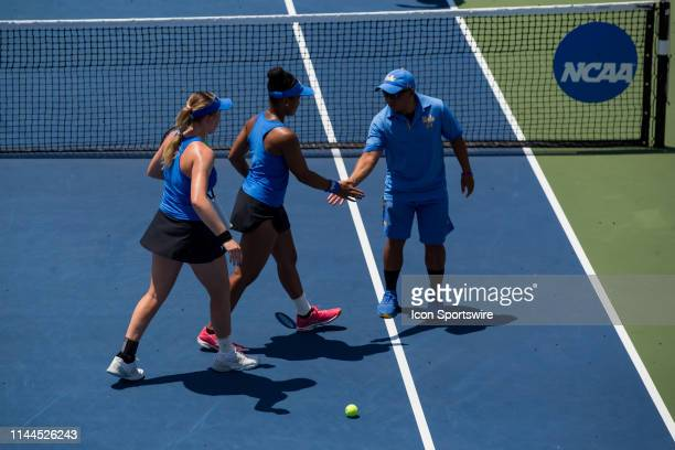 Women's tennis players Elysia Bolton and Jada Hart slap hands with assistant coach Giancarlo Cava during the quarterfinal round of the NCAA Division...