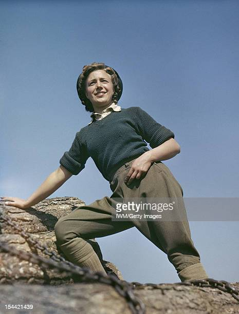 Women's Timber Corps Training Camp At Culford Suffolk Doreen Bacchus a Land Army girl standing on top of some tree trunks on a pull wagon circa 1942