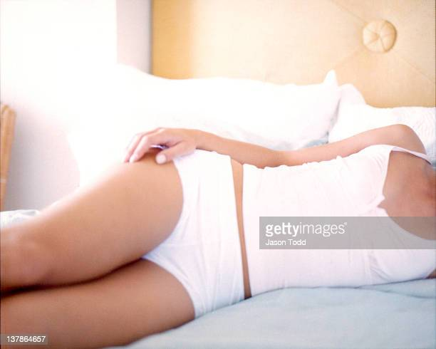 womens torso on hotel bed in underwear and camisal