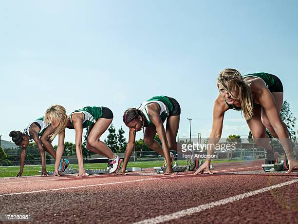 Women's track team at starting blocks