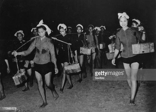 A women's unit carrying supplies to the south vietnam people's liberation army forces along the ho chi minh trail at night vietnam war 1968
