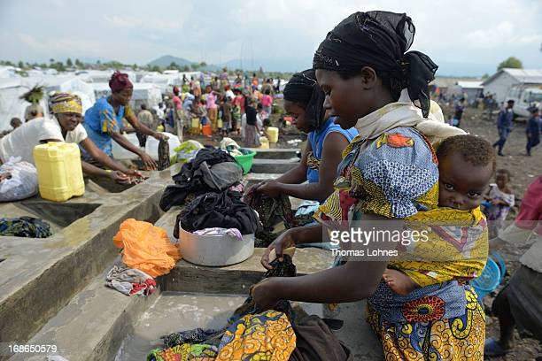 Womens washes clothes in camp Mugunga III for displaced persons on January 14 2013 in Goma Democratic Republic of Congo The war in Congo which has...