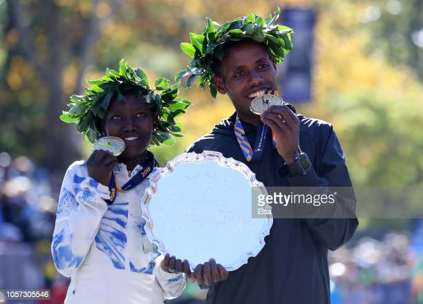 Women's winner Mary Keitany of Kenya and Men's winner Lelisa Desisa of Ethiopia pose with their medals at the finish line during the 2018 TCS New...