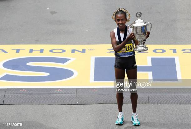 Women's winner Worknesh Degefa holds the trophy at the finish line of the 123rd Boston Marathon in Boston on April 15 2019