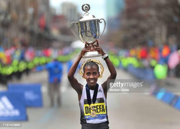 Women's winner Worknesh Degefa holds up her trophy after winning the 123rd Boston Marathon in Boston on April 15 2019