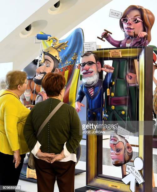 Woment look at a Ninot a doll depecting a celebrity representing Spain's Primer Ministre Mariano Rajoy Defense minister Maria Dolores de Cospedal and...