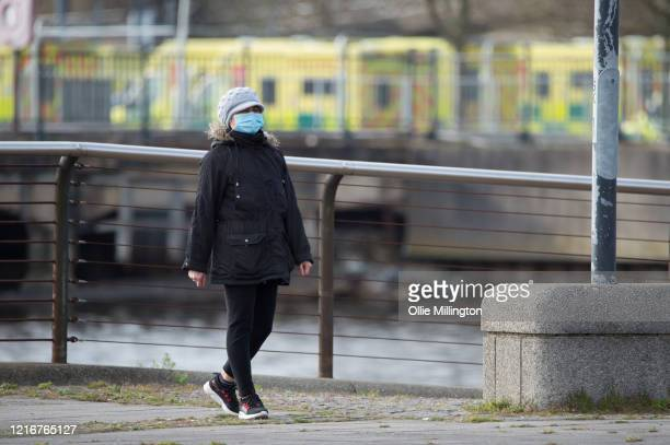A womenwearing a protective mask walks past the ExCeL London exhibition centre turned into NHS Nightingale field hospital on April 3 2020 in London...