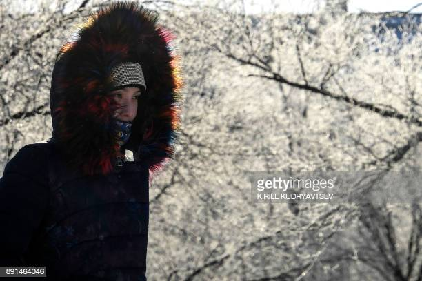 A womman walks past snowcovered trees in Baikonur city near the Russian leased Kazakh Baikonur cosmodrome on December 13 2017 The temperature in...