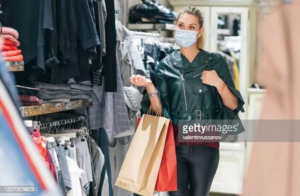 wom'n trägt schutzmaske und einkaufen nach wiedereröffnung der läden nach covid-19 - einkaufen stock-fotos und bilder