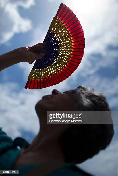 A wonam covers form the sun with a Spanish republican coloured fan after a protest calling for a Referenderum surrounding the Spnish Parliament at...