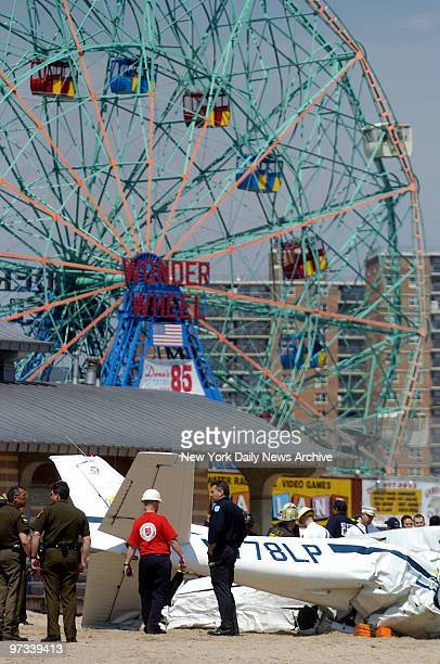 Wonder Wheel towers in the background as emergency crews investigate the scene of a small plane crash on the beach at W 16th St on Coney Island Pilot...