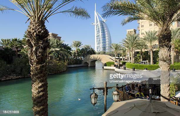 Wonderful 7 star Burj Al Arab hotel from the shopping mall at Madinat Jumeirah with boat and restaurants with palms in Dubai UAE inn thriving United...