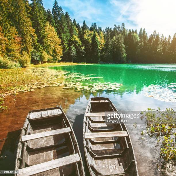Wonderful old weathered boat on riverbank of small altitude french Genin lake in middle of pine forest in Jura mountains