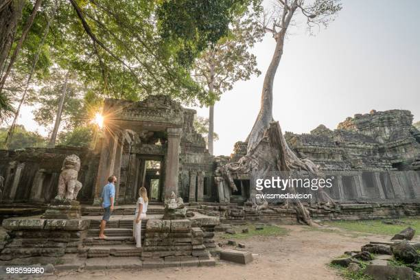 wonderlust- couple wandering in ancient temple with roots taking over old ruins- cambodia angkor wat complex at sunset - angkor wat stock pictures, royalty-free photos & images
