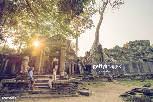 wonderlust- couple wandering in ancient temple with roots taking over old ruins- cambodia angkor wat complex at sunset - angkor stock photos and pictures