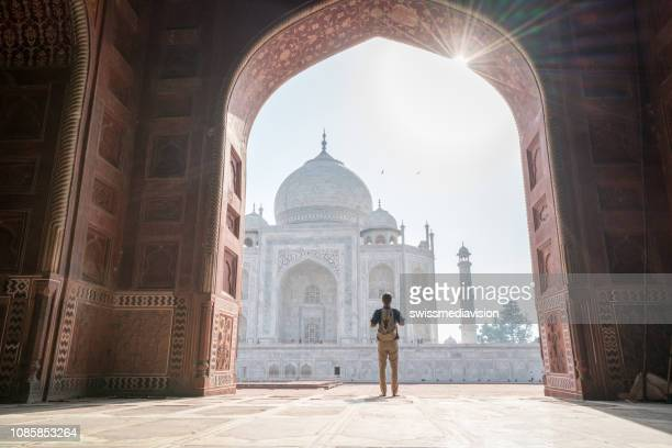 wonderlust man discovering beautiful taj mahal at sunrise - taj mahal stock photos and pictures