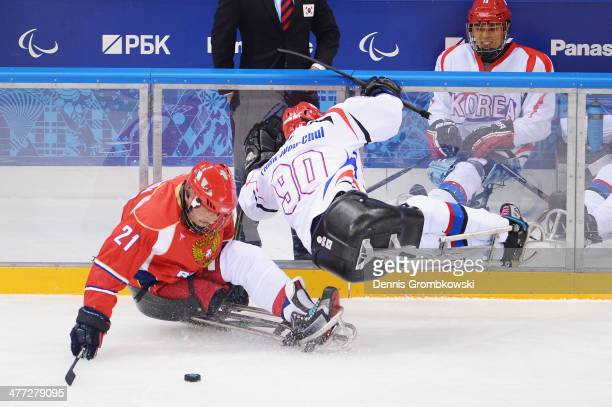 WooChul Park of Korea lifts up under the pressure of Evgeny Petrov of Russia during the Ice Sledge Hockey Preliminary Round Group A match between the...