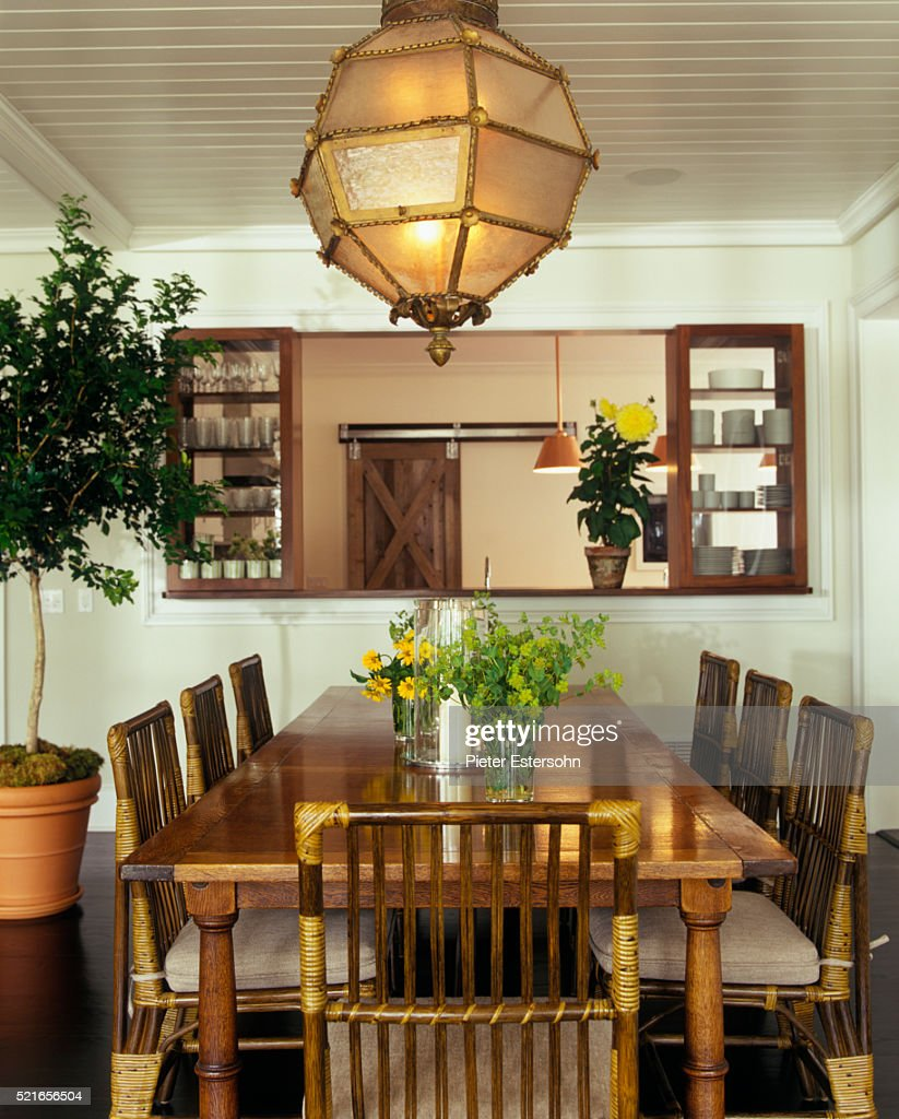 Wood And Rattan Dining Table Chairs Beneath Gold Light Fixture Stock Photo