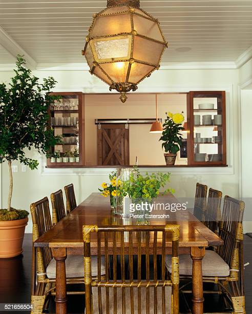 Wood and rattan dining table and chairs beneath gold light fixture