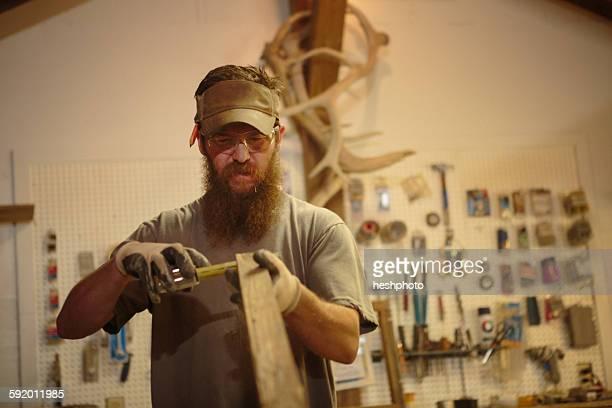 wood artist in workshop, measuring wood - heshphoto stock-fotos und bilder