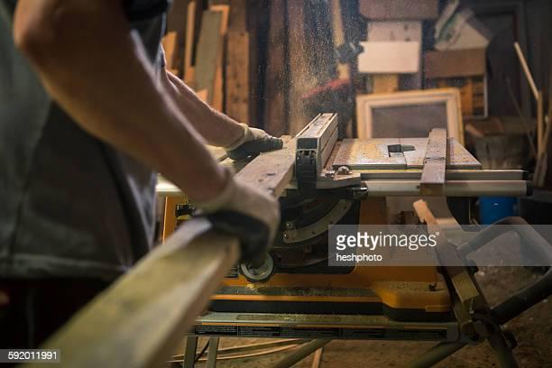 wood artist in workshop, using woodworking machinery, mid section - heshphoto stock-fotos und bilder