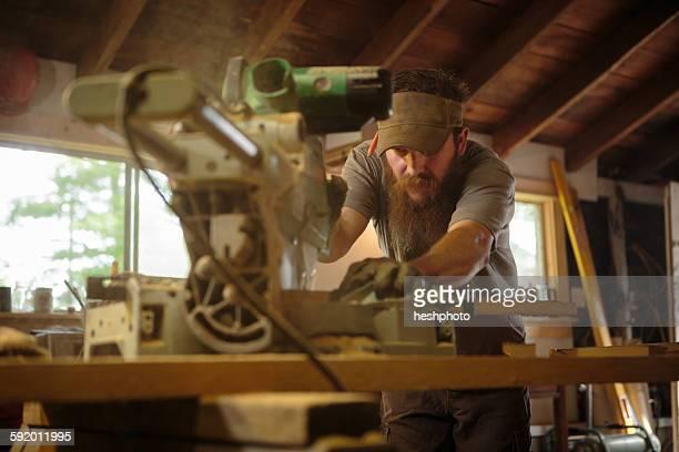 wood artist using machinery in workshop - heshphoto stock-fotos und bilder