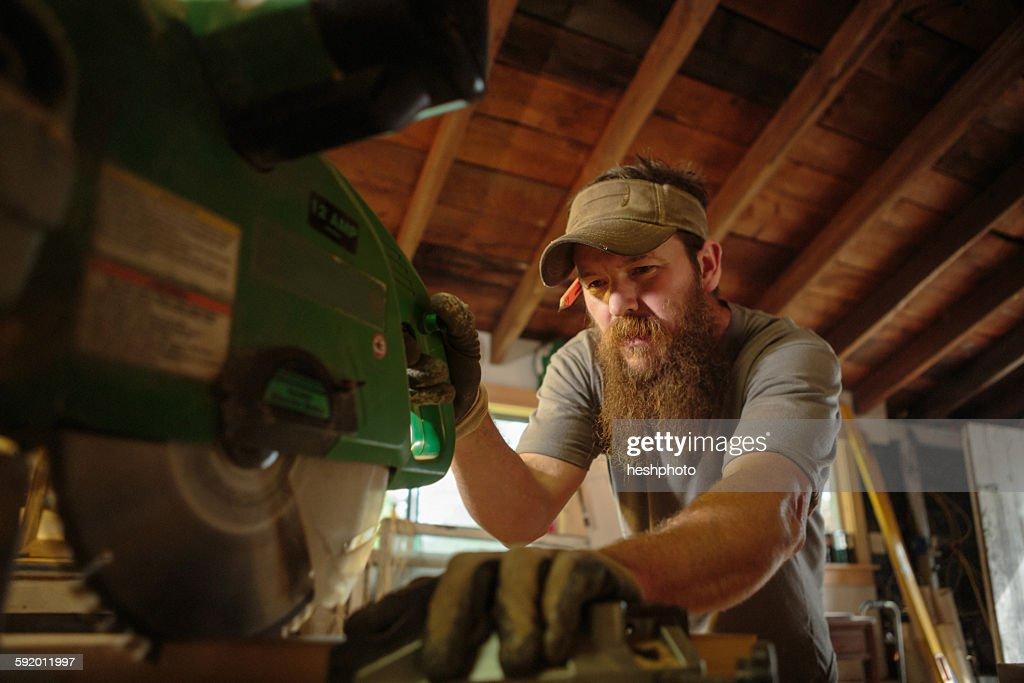 Wood artist using machinery in workshop : Stock Photo