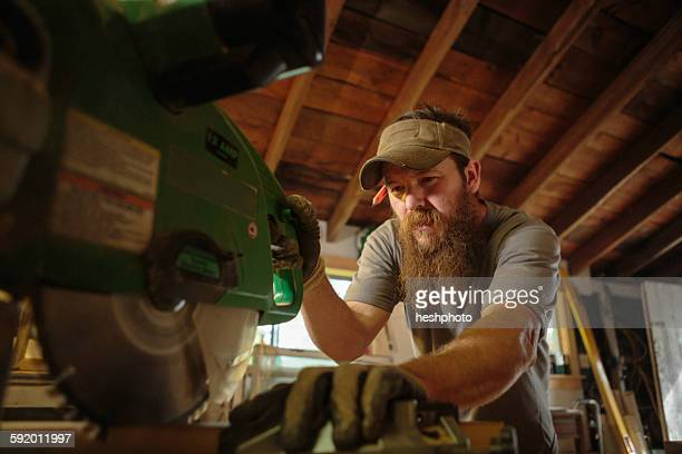 wood artist using machinery in workshop - circular saw stock photos and pictures