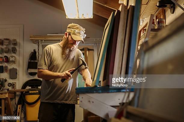 wood artist working in workshop, using hammer - heshphoto stock-fotos und bilder